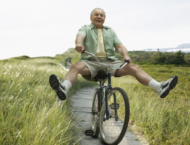 White-haired man rides excitedly on a bike