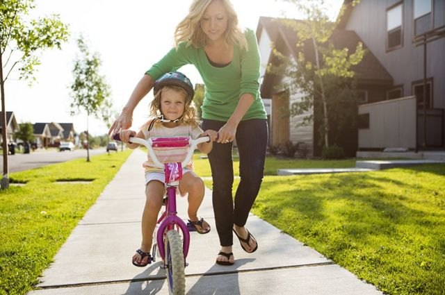 A young girl rides a bike with the help of a woman