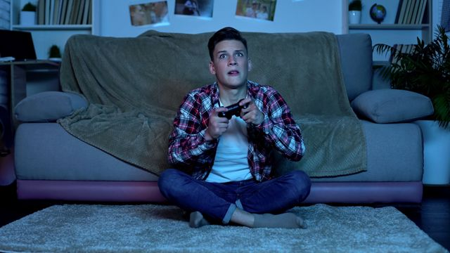 A young man controls video games and looks at TV