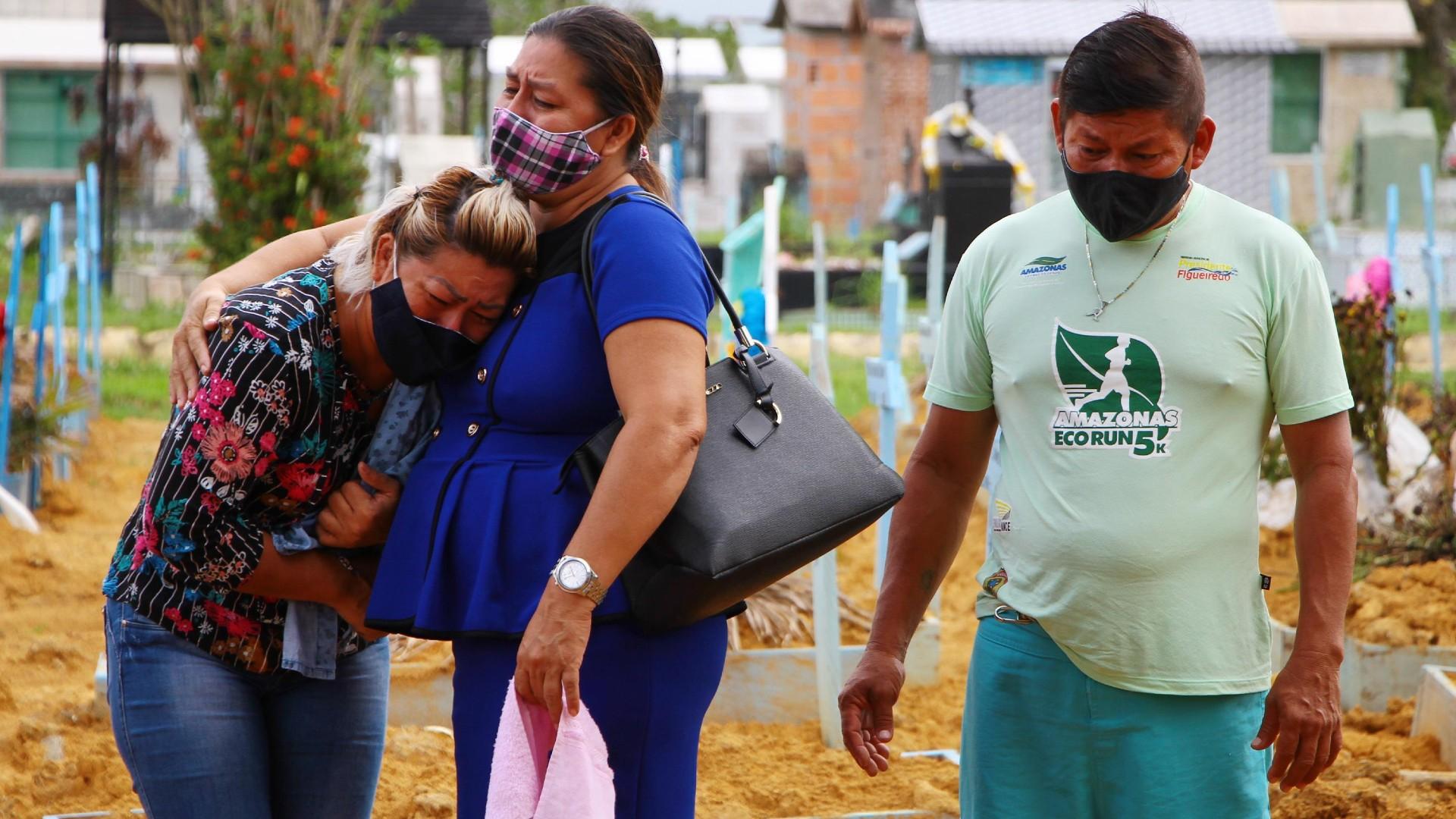 Familiares choram mortes de vítima de Covid-19 em enterro