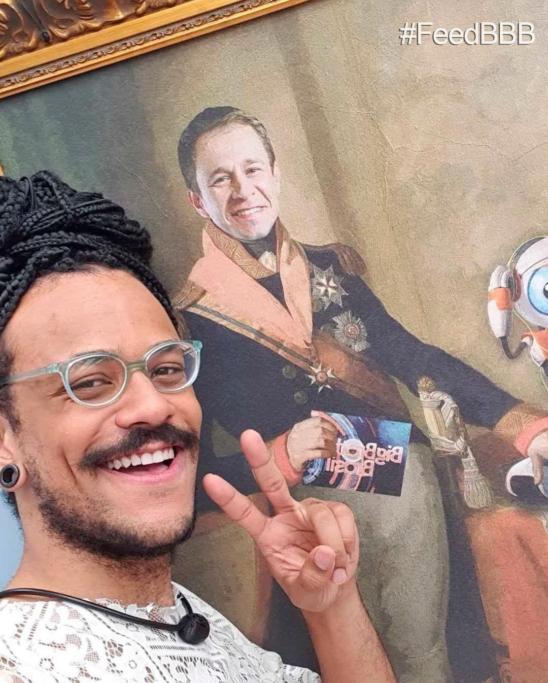 """Joao Luiz poses with a painting of Thiago Levert in the leader's room that day """"BBB 101 Day"""" - clone / Instagram"""
