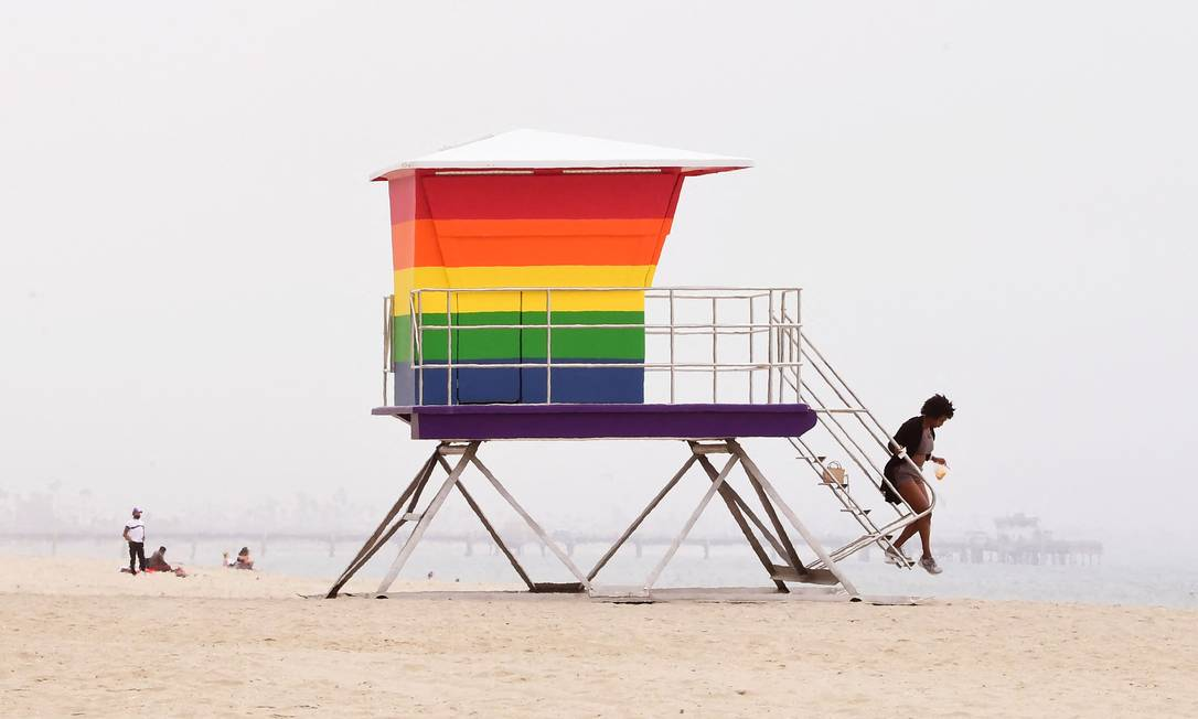 A woman descends the rainbow staircase of the Lifeguard Tower in Long Beach, California.  A new outpost for LGBTQ Pride month opened after vandals set it on fire in March Photo: FREDERIC J. BROWN/AFP