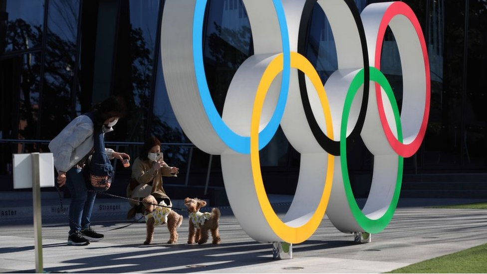 People interact on a public bench behind the Olympic symbol